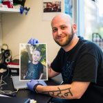 Ryan Kohn, a PhD candidate in the MIT Biology Department's Jacks Lab, holds a photo of his son, Jayden.
