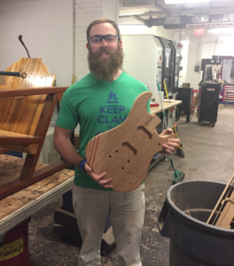 student holding wood guitar he made