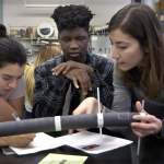 Instructor Michela Geri (right) guides students Omoruyi Atheka (center) and Aline Vargas as they evaluate how their intuition of torsion measures up to their experimental results.