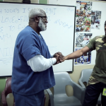A mentor in the South Bay House of Correction shakes hands with an MIT st