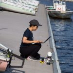 Charlene Xia, pictured at the MIT Sailing Pavilion, tests her microbiome monitoring system in the Charles River.